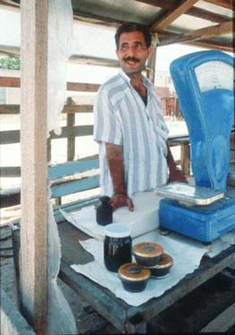 Икру добытую на каспийском побережье продает улыбчивый мужчина с загорелым лицом